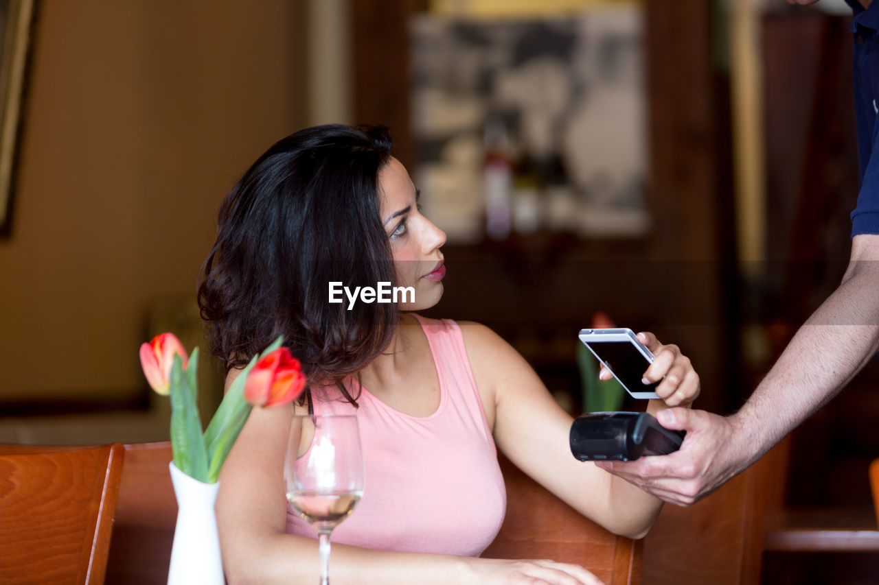 holding, real people, lifestyles, mobile phone, focus on foreground, portable information device, indoors, smart phone, young adult, young women, women, wireless technology, communication, sitting, leisure activity, one person, restaurant, adult, technology, casual clothing, glass, hairstyle