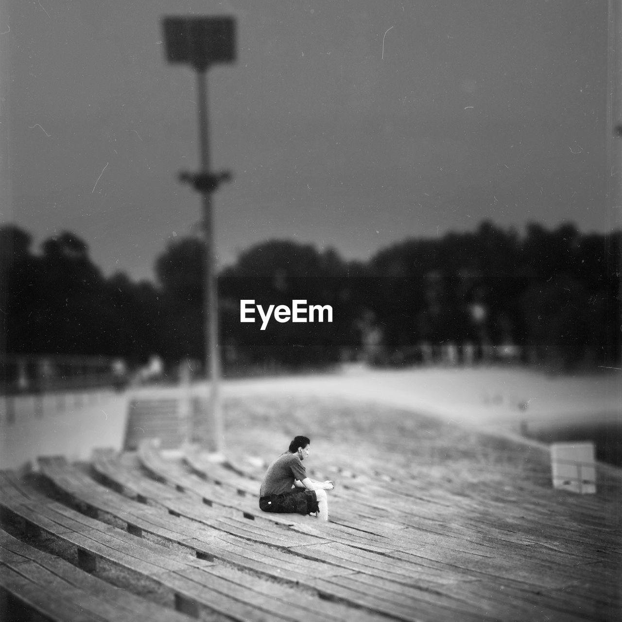 Man Relaxing On Bleachers In Stadium