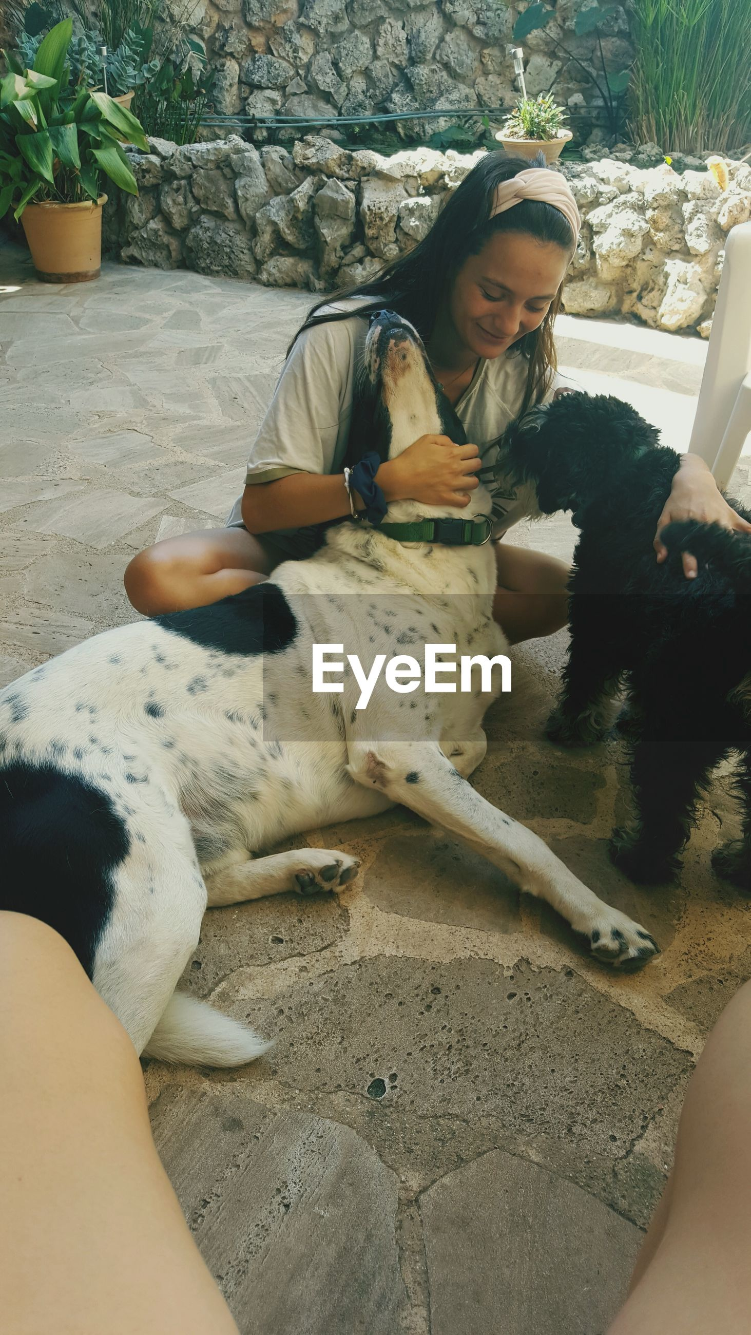 dog, pets, domestic animals, togetherness, animal themes, real people, mammal, relaxation, leisure activity, friendship, day, bonding, lying down, sitting, lifestyles, young women, young adult, outdoors, people