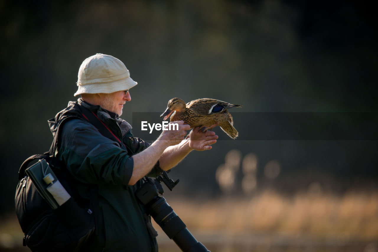 Side View Of Man Holding A Duck