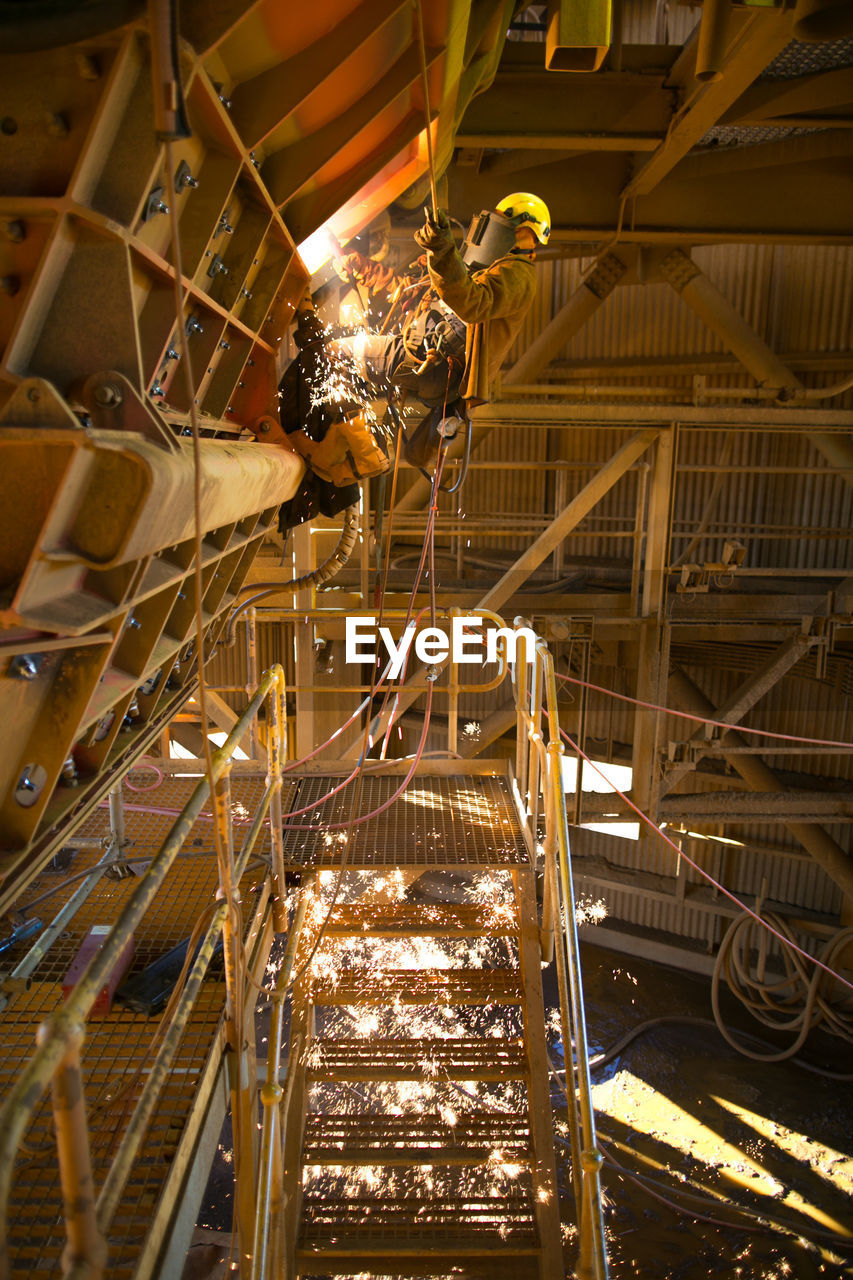 industry, factory, illuminated, indoors, machinery, no people, low angle view, welding, technology, metal, lighting equipment, construction industry, architecture, business, working, production line, built structure, motion, electricity, glowing, ceiling, metal industry, industrial equipment