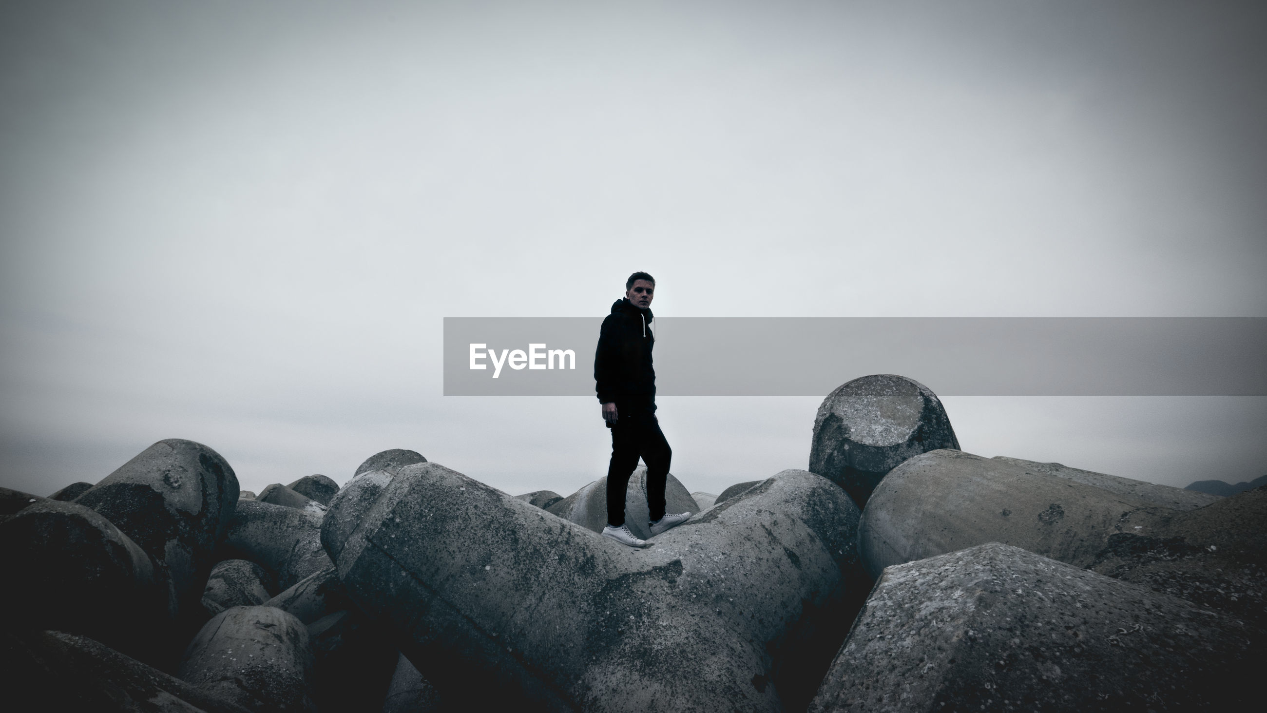 Portrait of young man standing on tetrapod at beach against sky