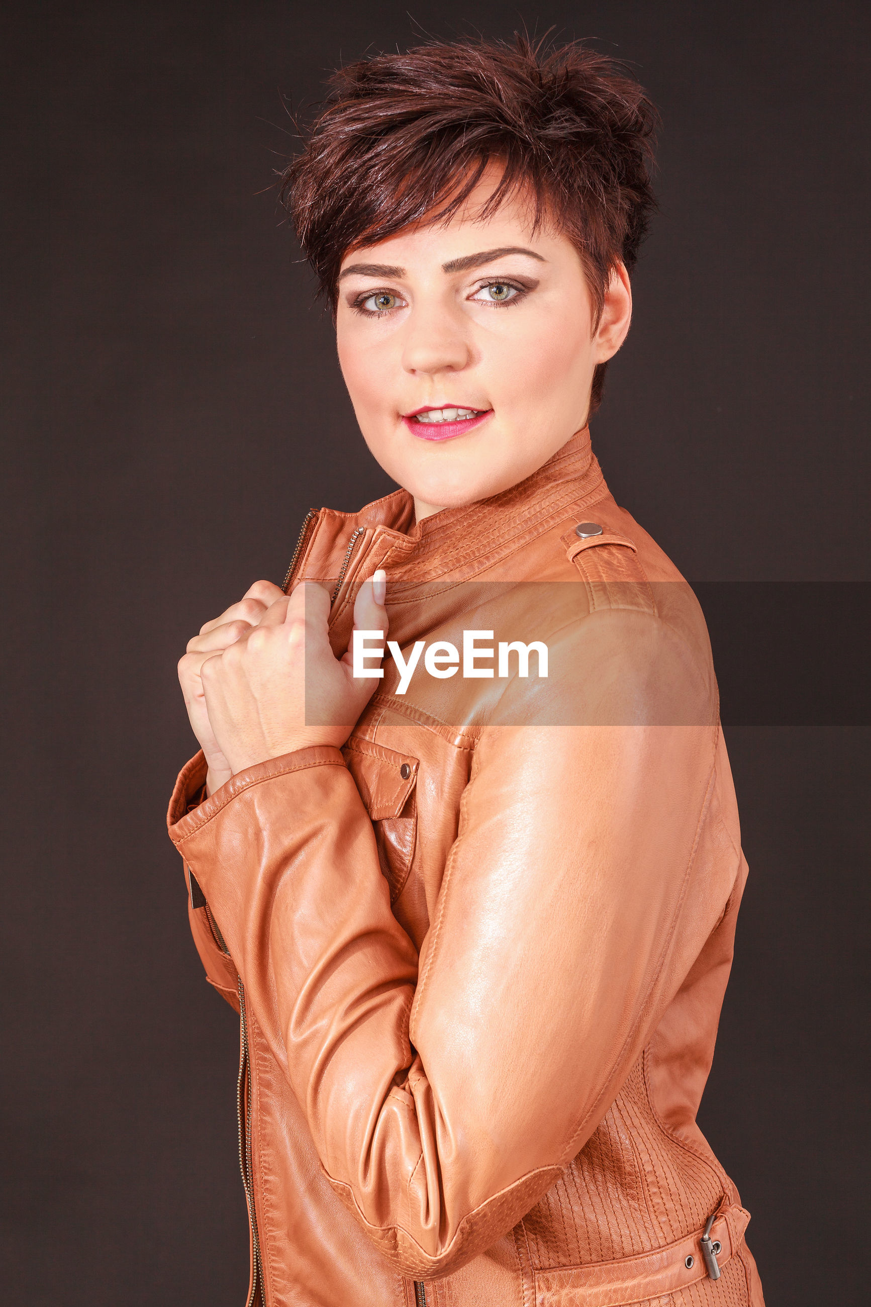 Portrait of female model wearing brown leather jacket against gray background