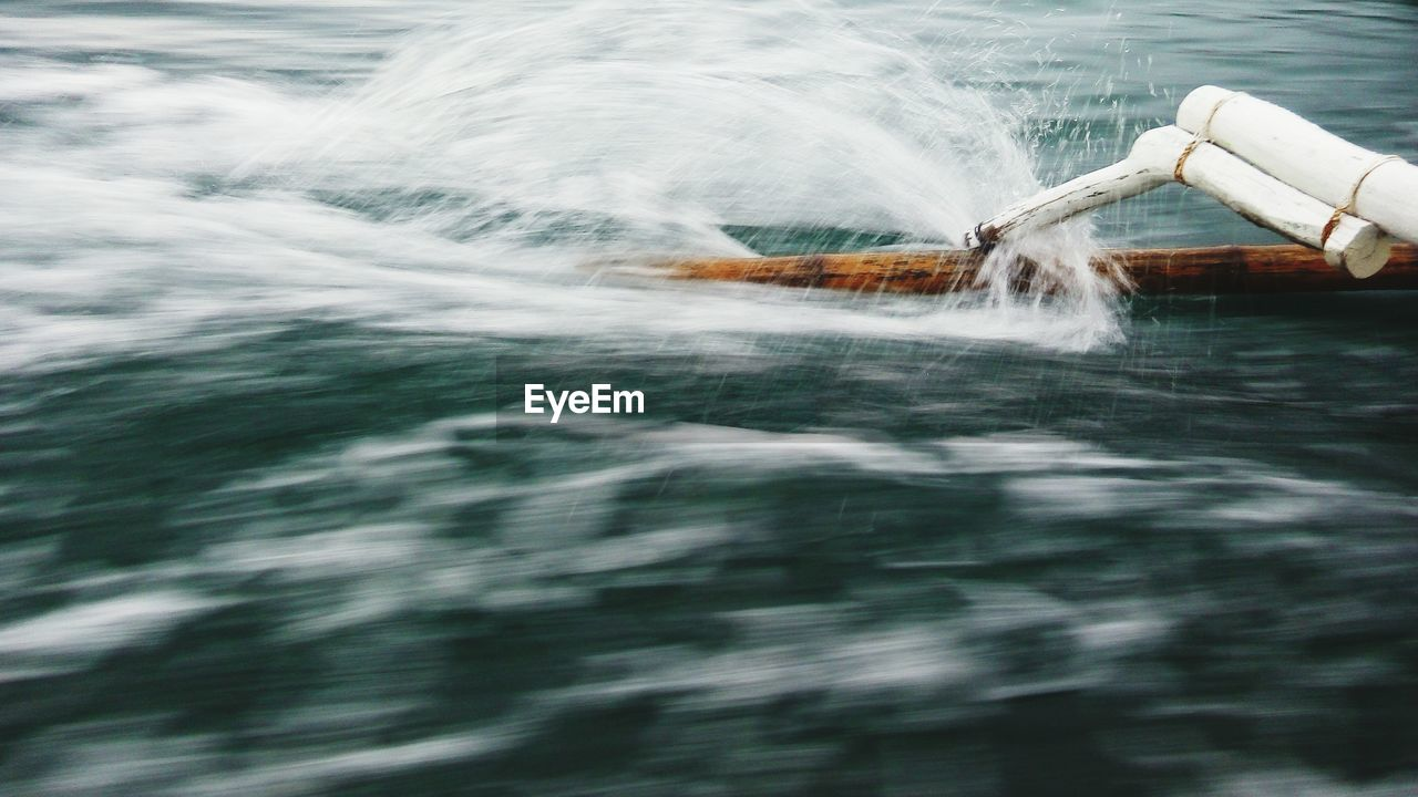 Cropped image of outrigger boat sailing in sea