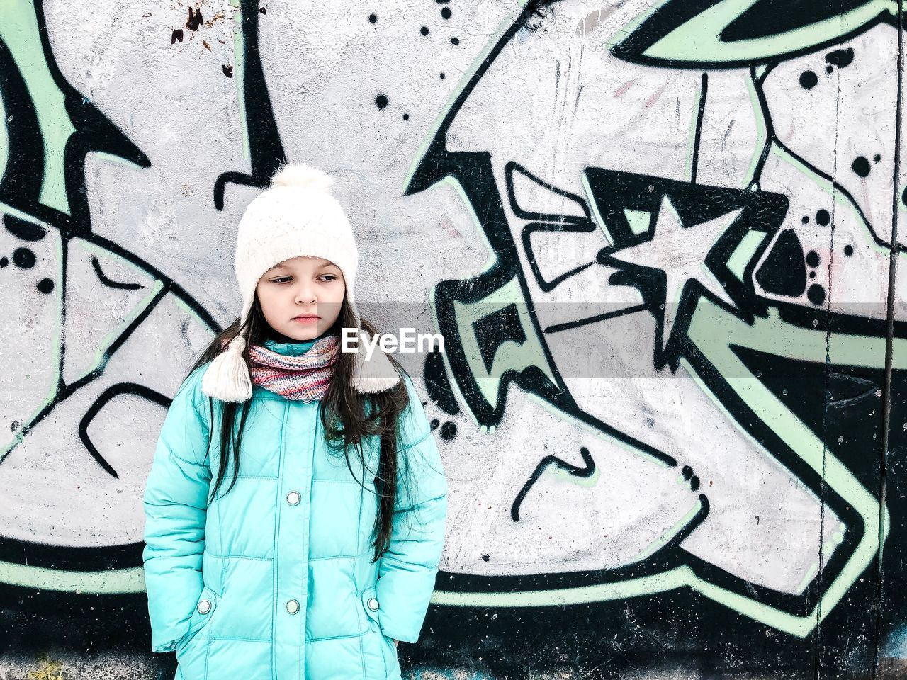 one person, graffiti, child, clothing, portrait, hat, standing, winter, childhood, warm clothing, looking at camera, women, females, day, knit hat, wall - building feature, waist up, city, outdoors