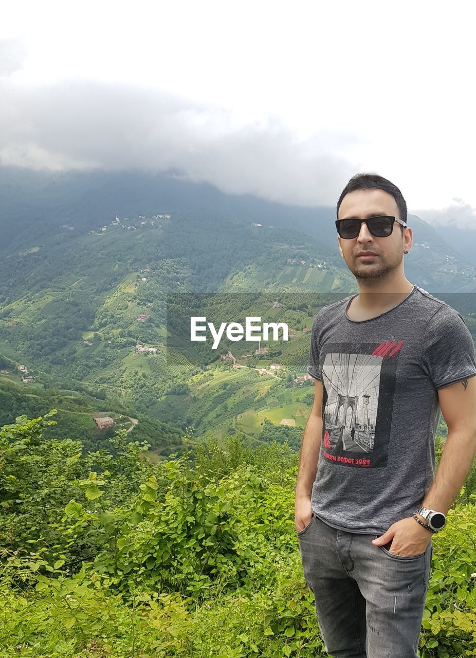 one person, casual clothing, sunglasses, standing, glasses, young adult, young men, real people, front view, fashion, lifestyles, nature, leisure activity, scenics - nature, three quarter length, beauty in nature, mountain, plant, green color, tranquility, outdoors