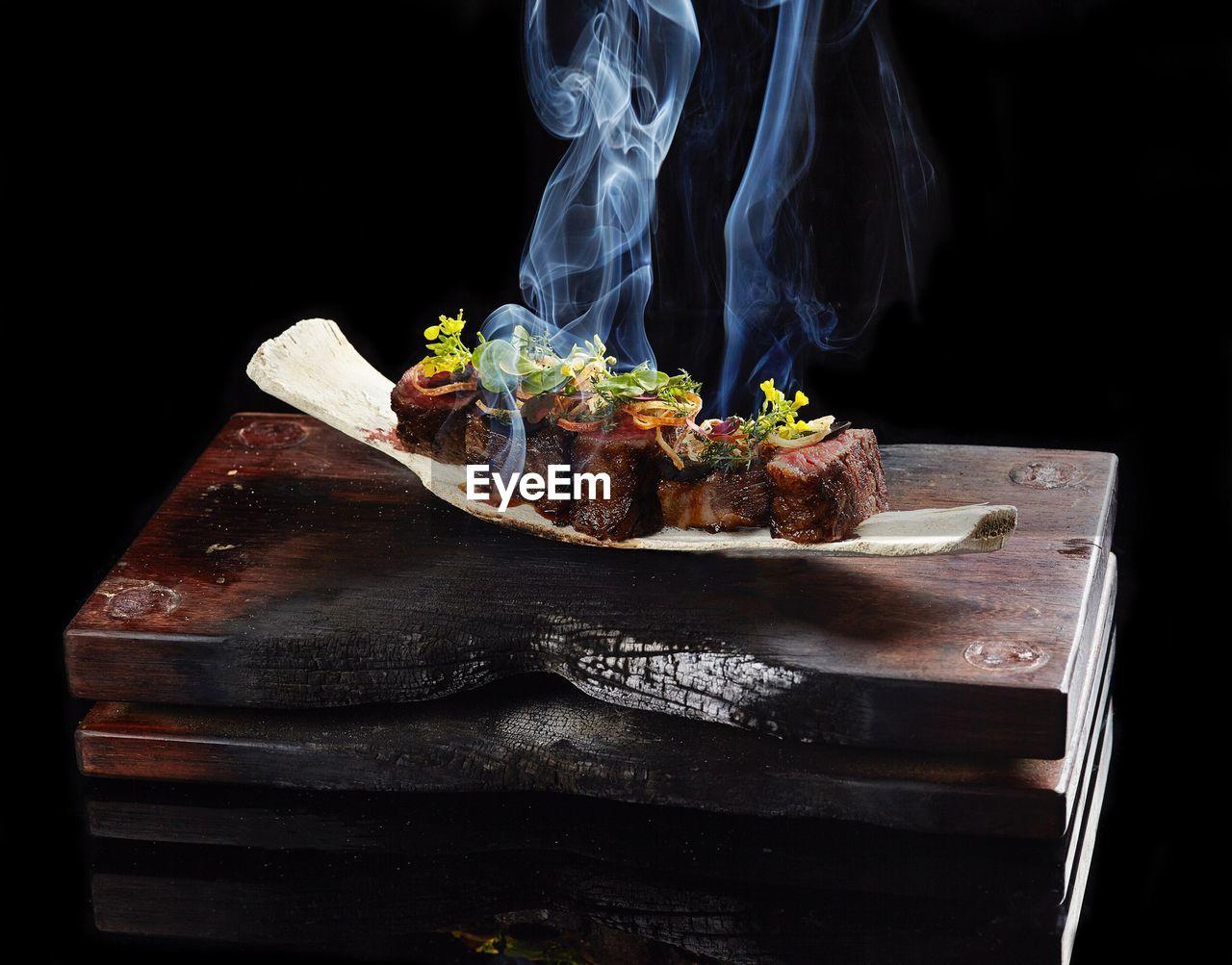 Steamed meat on wood against black background