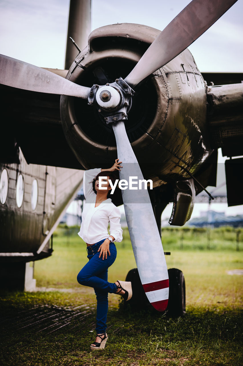 Woman Standing Against Airplane On Field