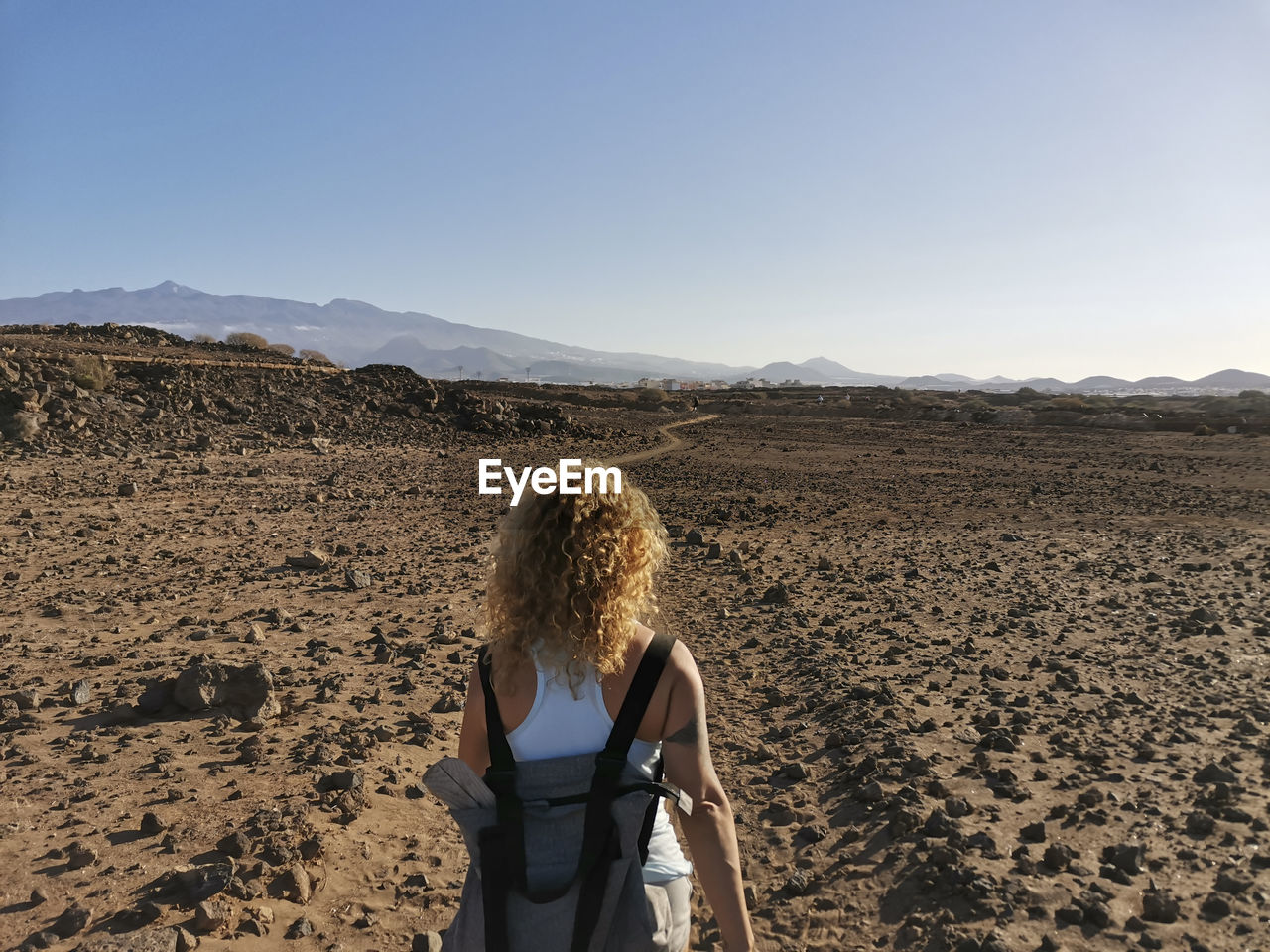 Rear view of woman standing on land against sky