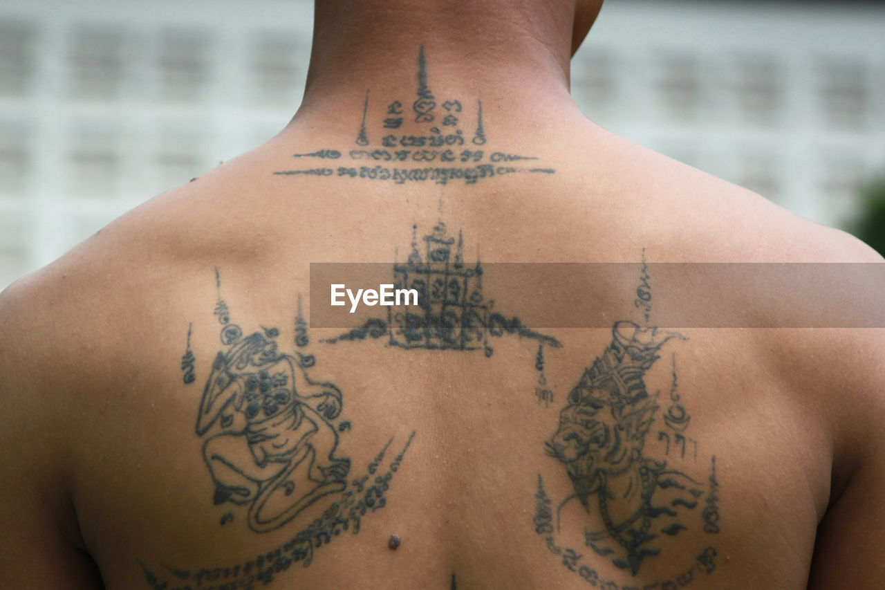 tattoo, human body part, shirtless, real people, text, midsection, human back, skin, human skin, indoors, design, lifestyles, creativity, one person, women, art and craft, body part, focus on foreground, rear view, floral pattern, hand, human limb, human arm