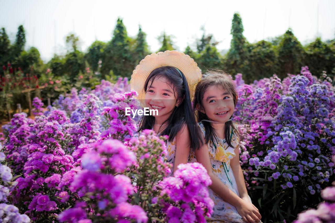 Portrait of smiling girl against purple flowering plants