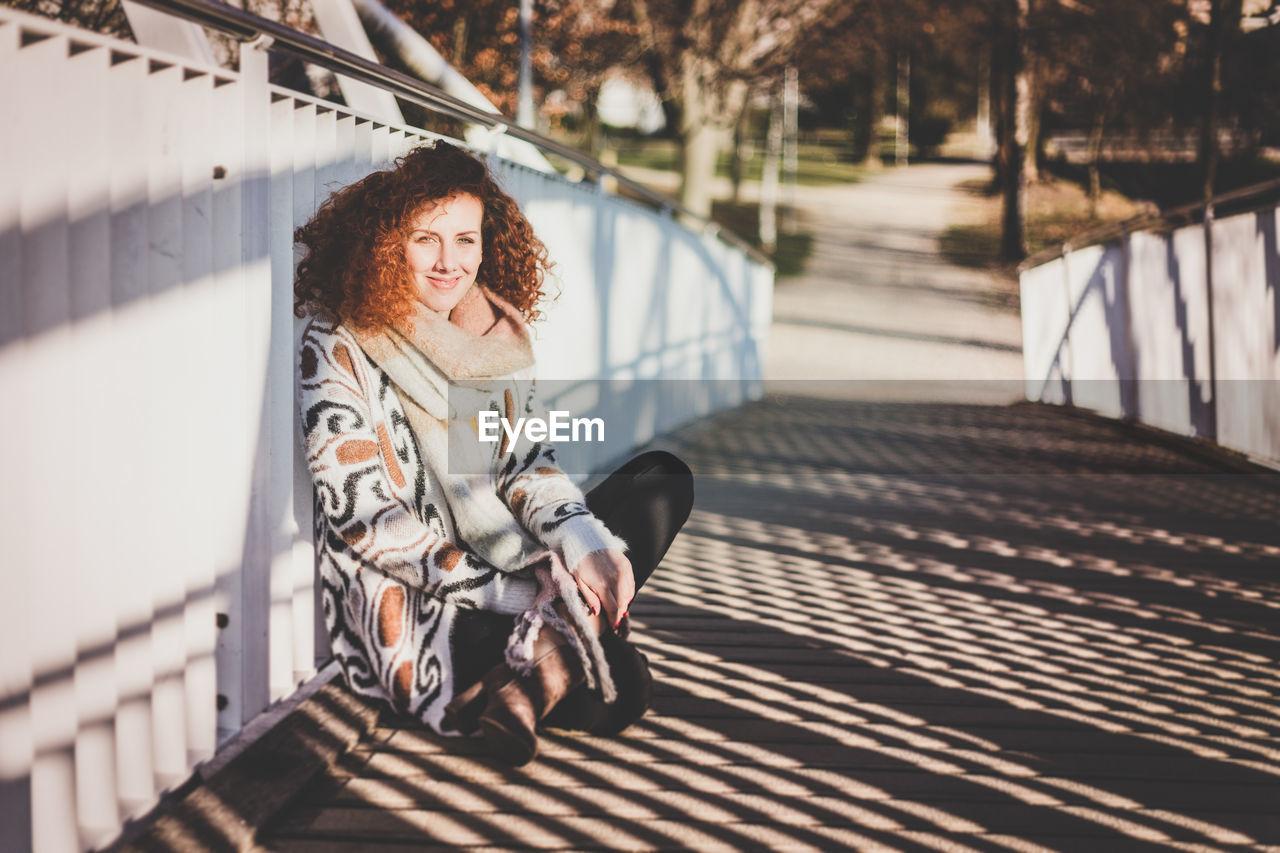 Portrait Of Smiling Woman Sitting On Footbridge