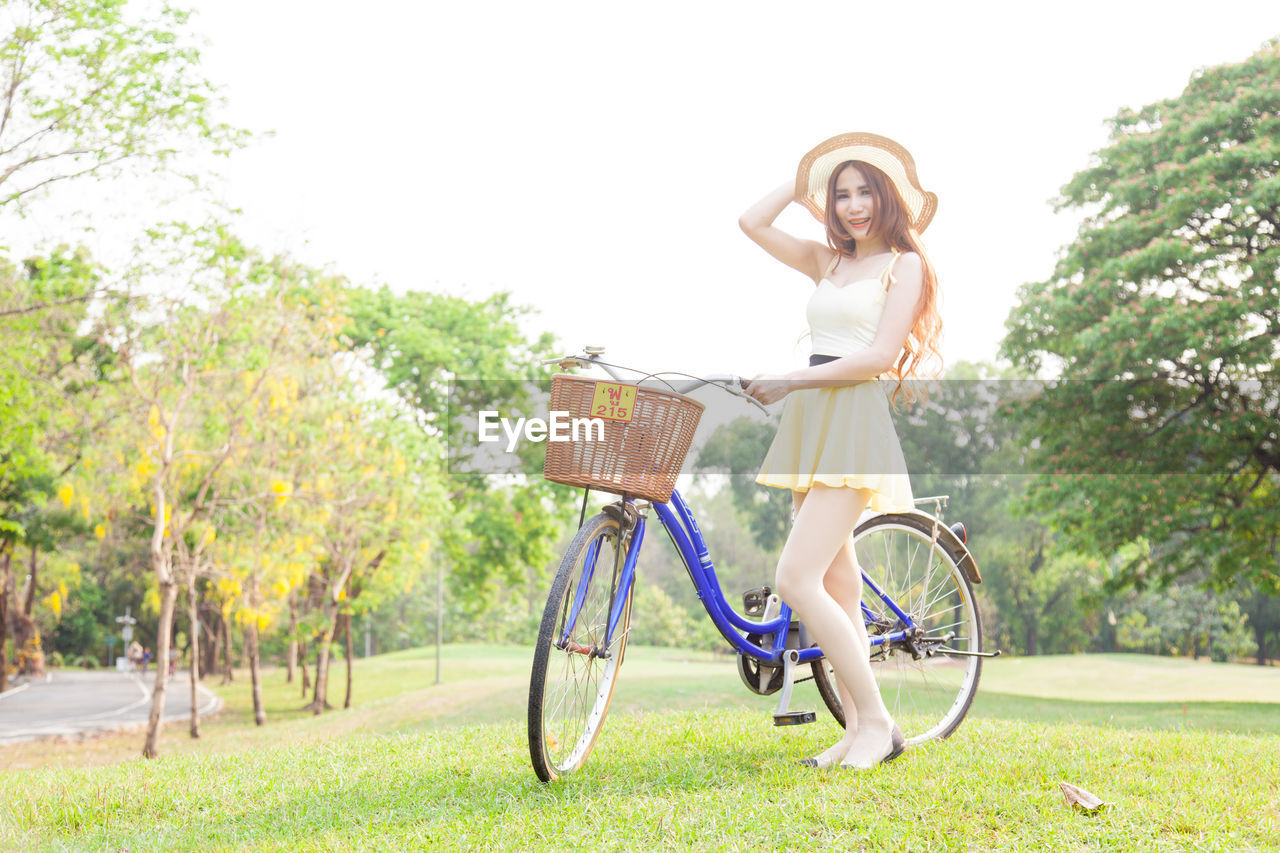 Full Length Of Woman With Bicycle Standing On Grass Field Against Sky