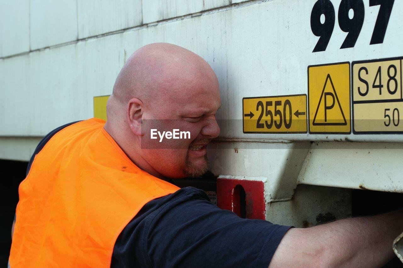 Mid adult man pushing truck