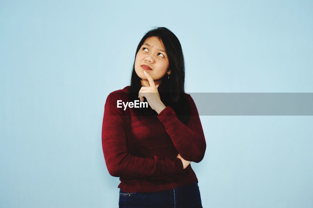 YOUNG WOMAN LOOKING AWAY AGAINST BLUE BACKGROUND