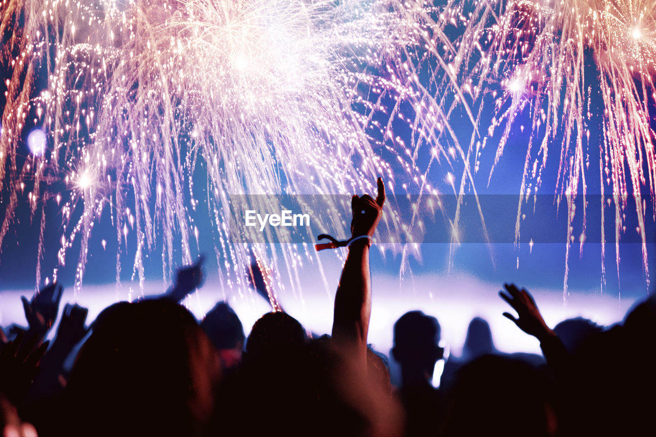 Crowd At Music Concert Against Firework During Night