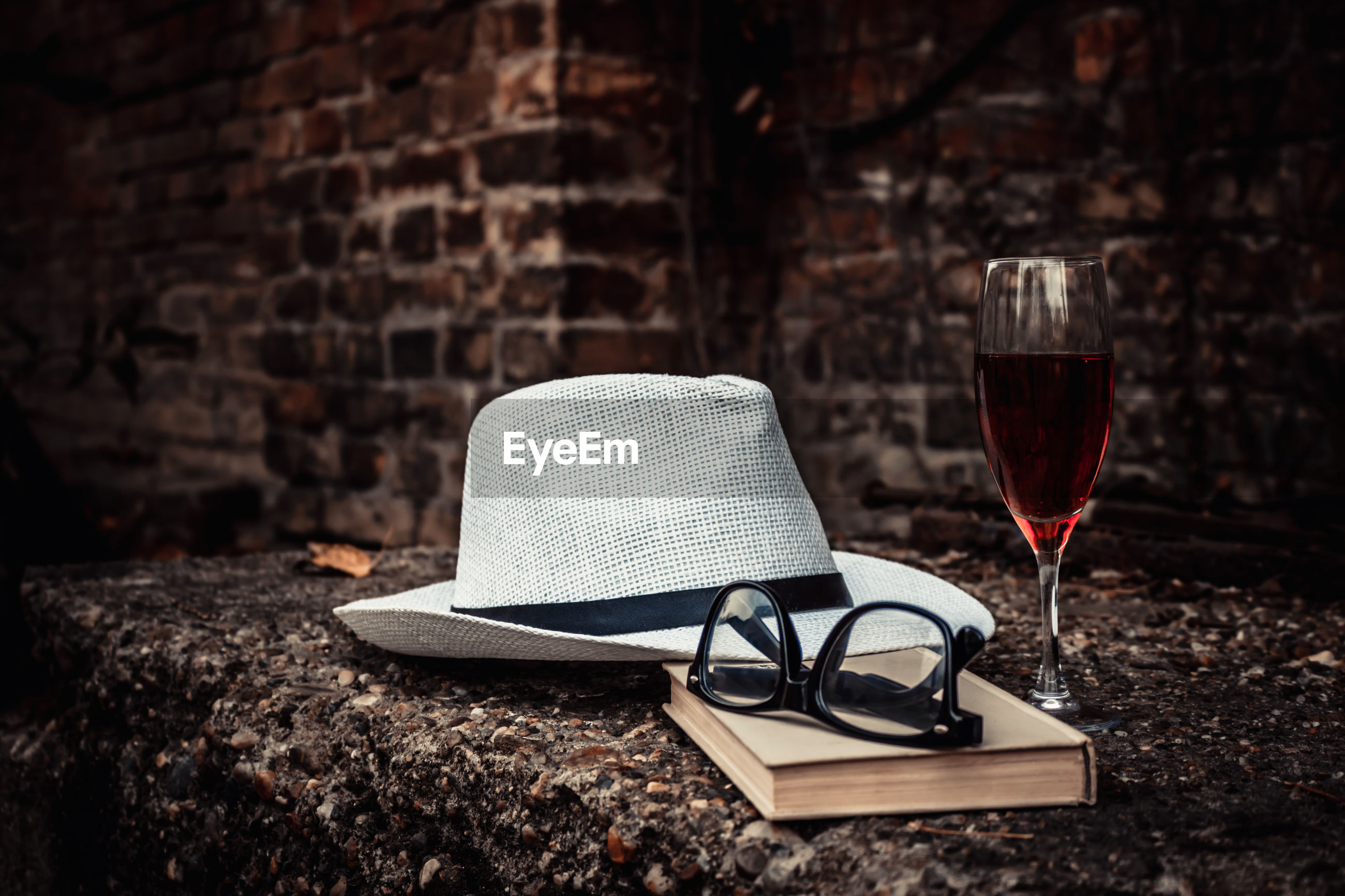 Fedora hat with book and glass of red wine.