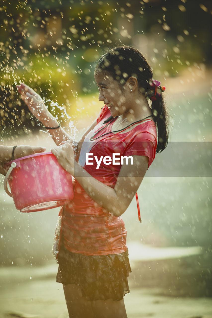 Playful girl splashing water while standing on street