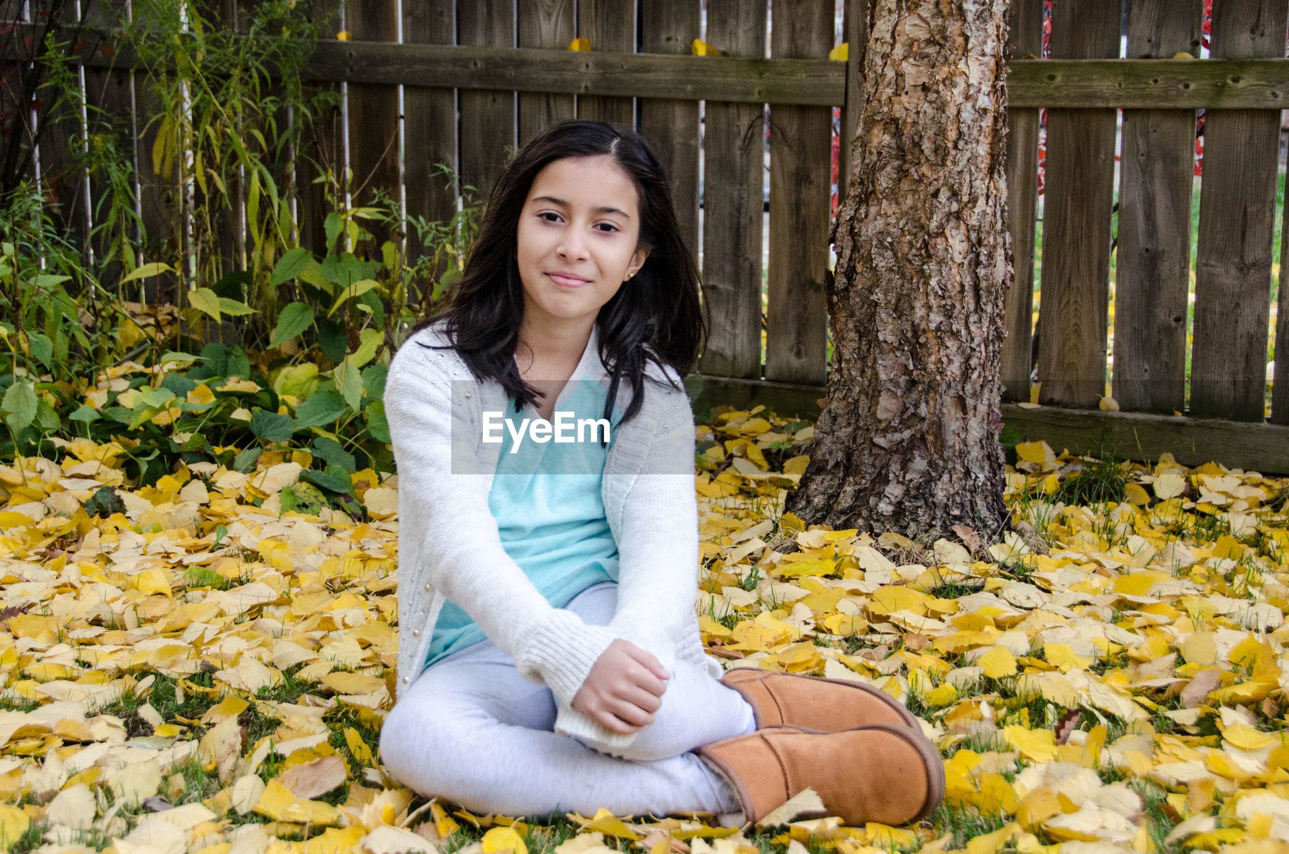 Portrait of smiling girl sitting on leaves covered field during autumn