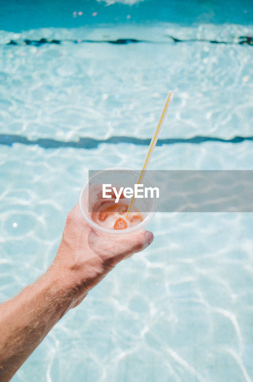 human hand, human body part, hand, real people, water, drinking straw, straw, one person, holding, food and drink, drink, refreshment, swimming pool, pool, nature, day, body part, sea, glass, outdoors, finger