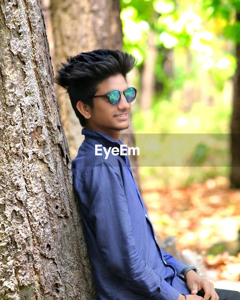 real people, sunglasses, one person, smiling, lifestyles, young adult, leisure activity, outdoors, tree, focus on foreground, eyeglasses, casual clothing, tree trunk, young men, looking at camera, glasses, day, happiness, standing, portrait, young women, posing, nature