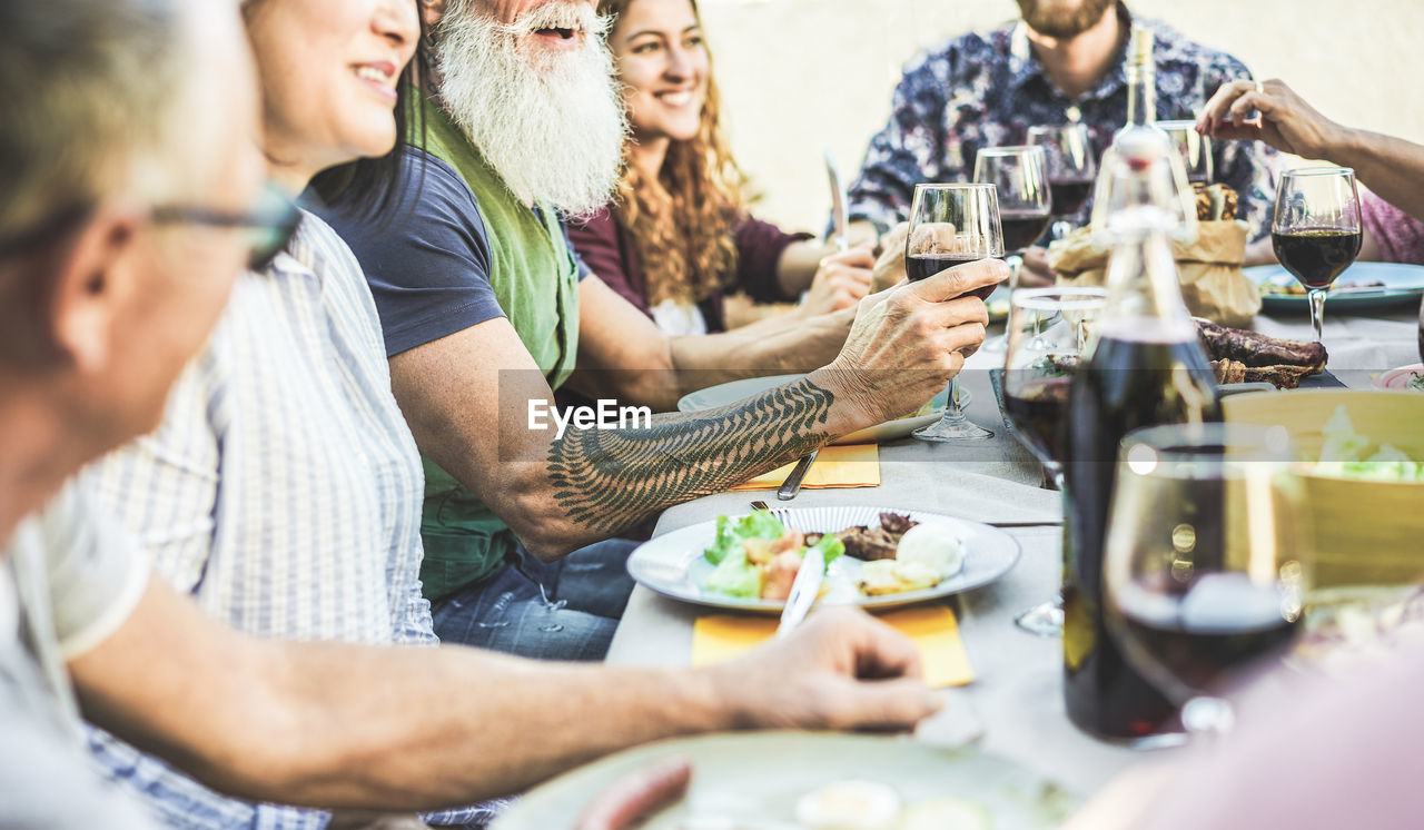 food and drink, selective focus, real people, men, group of people, table, food, women, lifestyles, adult, togetherness, males, plate, people, casual clothing, mature adult, sitting, females, mature men, leisure activity, glass