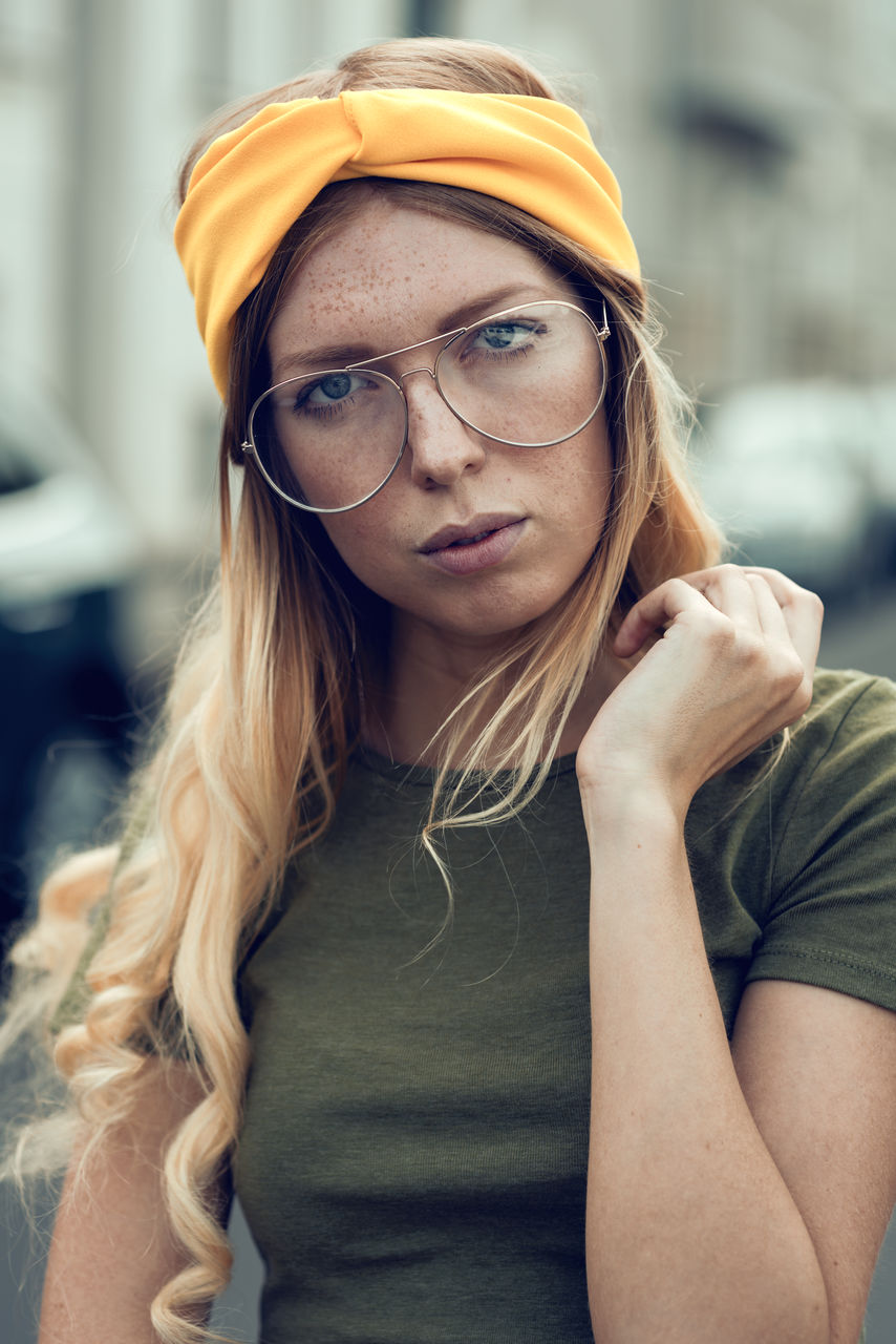 Portrait Of Woman In Eyeglasses And Yellow Headband Outdoors