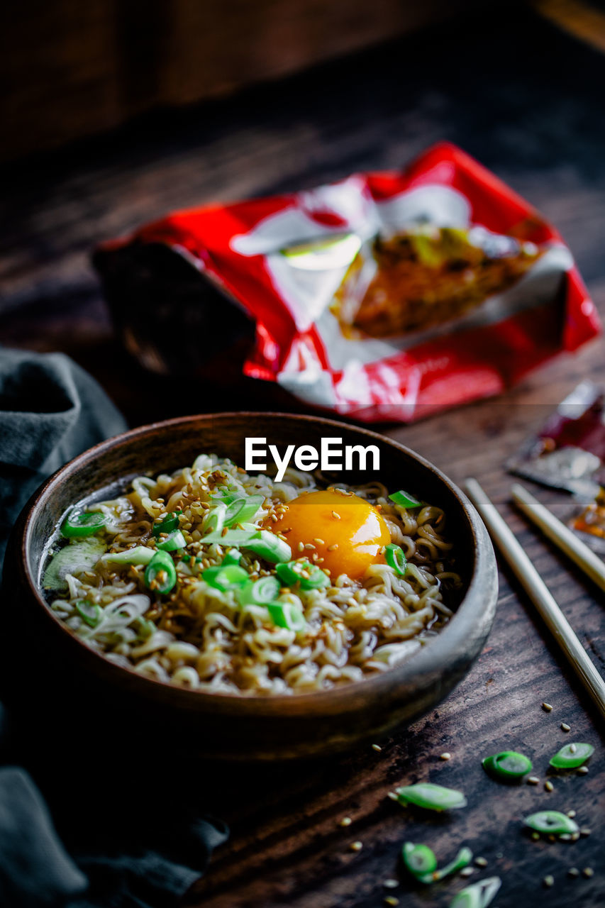High angle view of instant ramen noodle soup served on wooden table