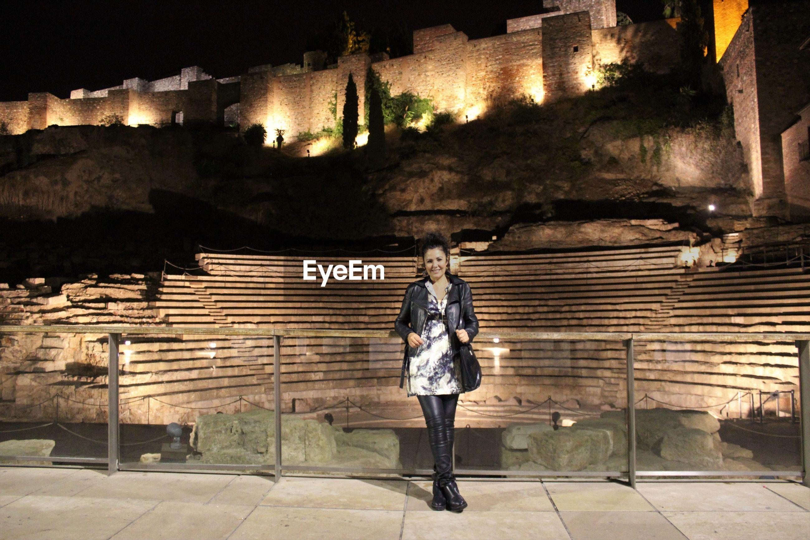 Full length of woman in illuminated city at night