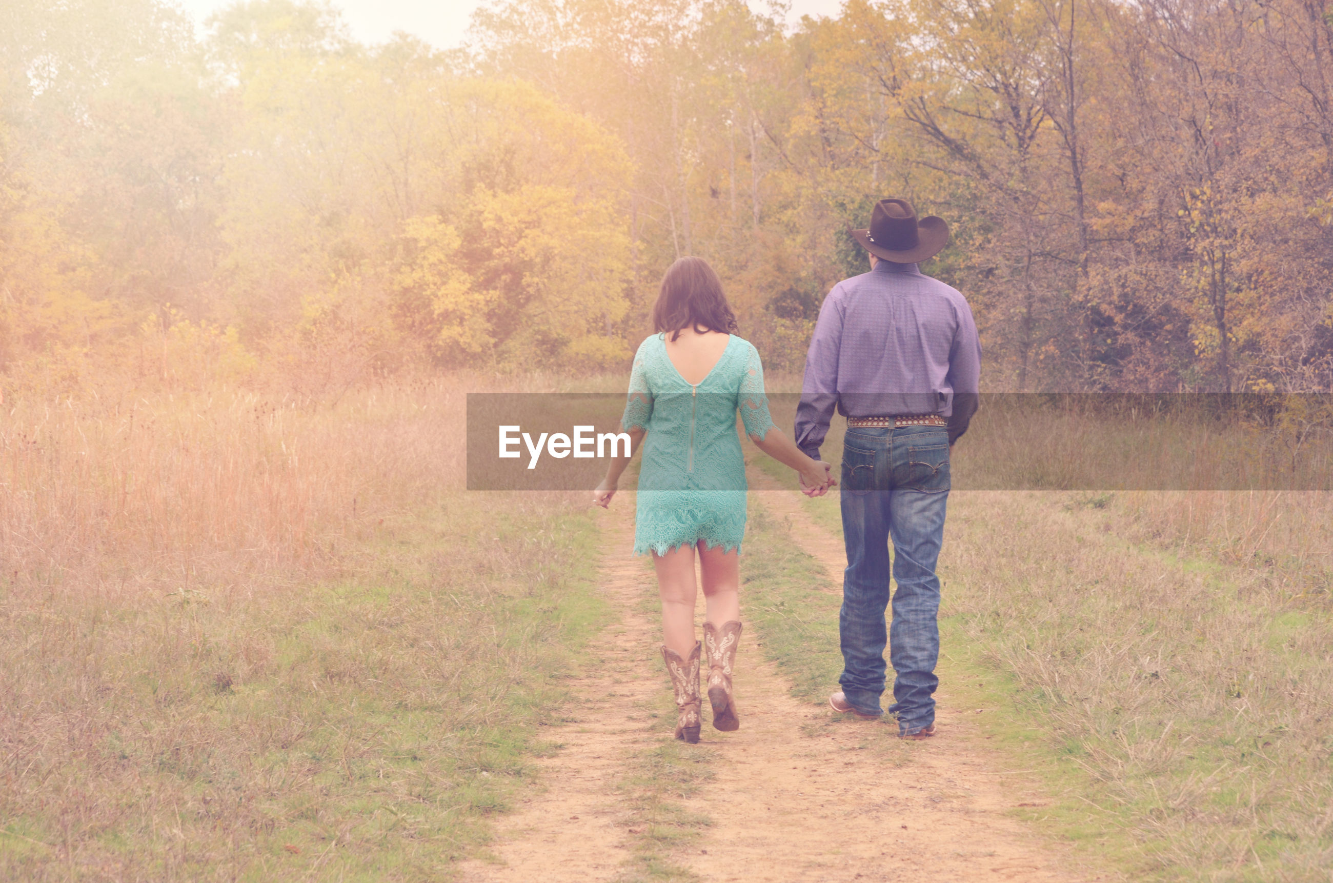 Rear view of couple walking on footpath