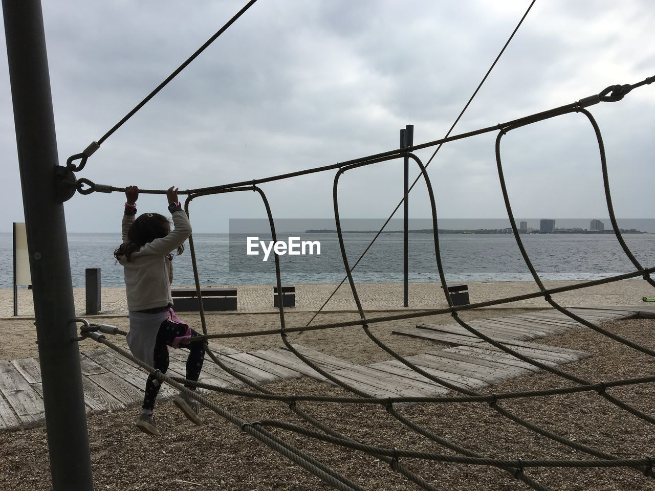 Rear view full length of girl on jungle gym by sea