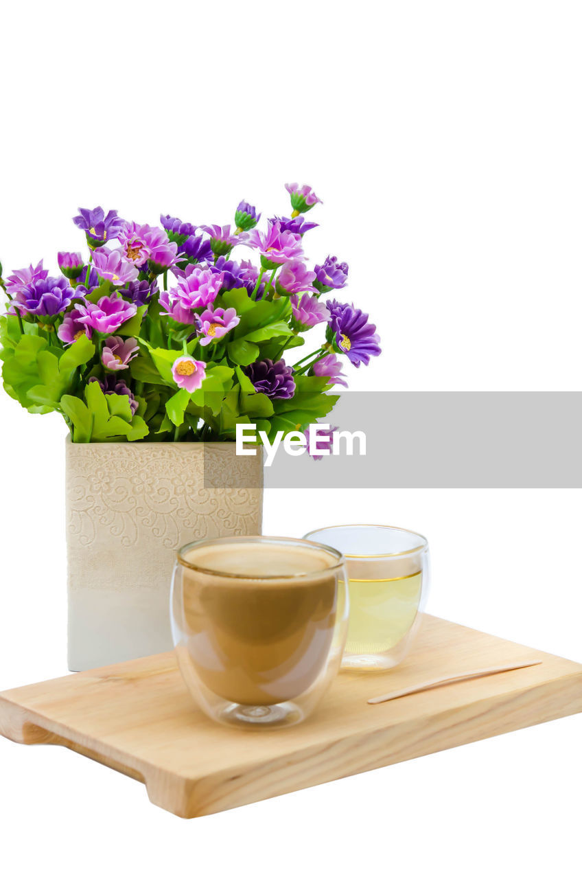 flowering plant, flower, freshness, white background, plant, vase, refreshment, cup, indoors, studio shot, drink, table, no people, still life, mug, glass - material, nature, food and drink, glass, close-up, flower head, purple, flower arrangement