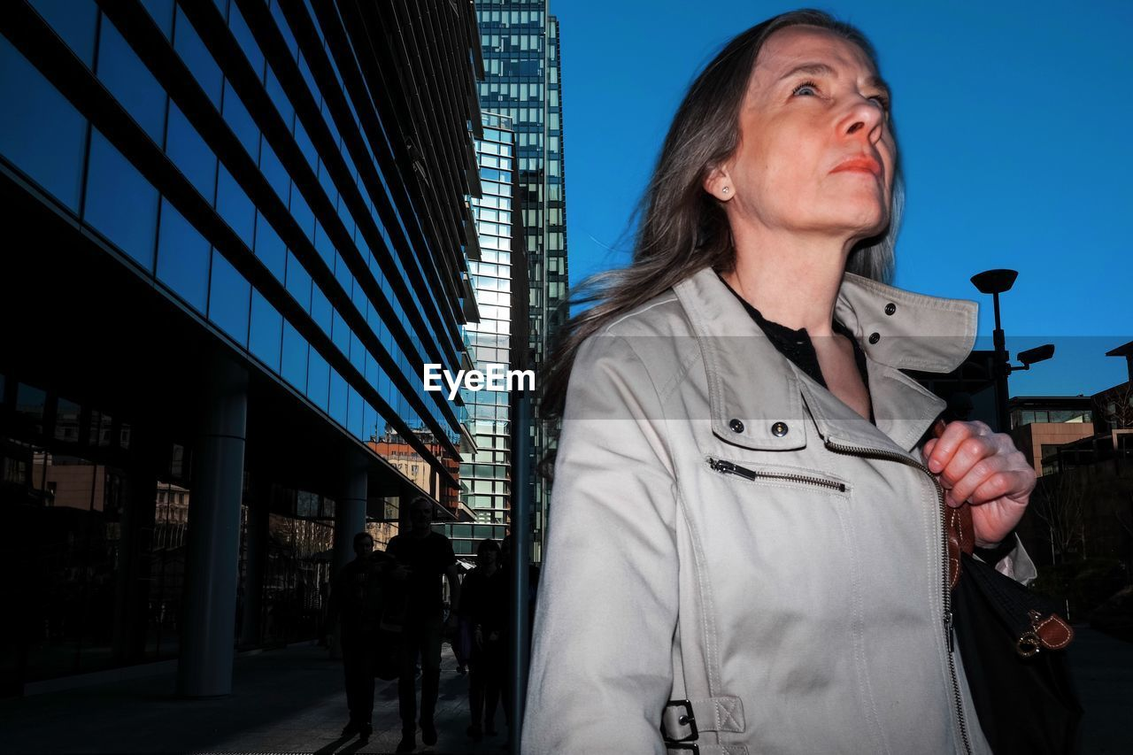 FULL LENGTH OF WOMAN STANDING AGAINST SKY IN CITY
