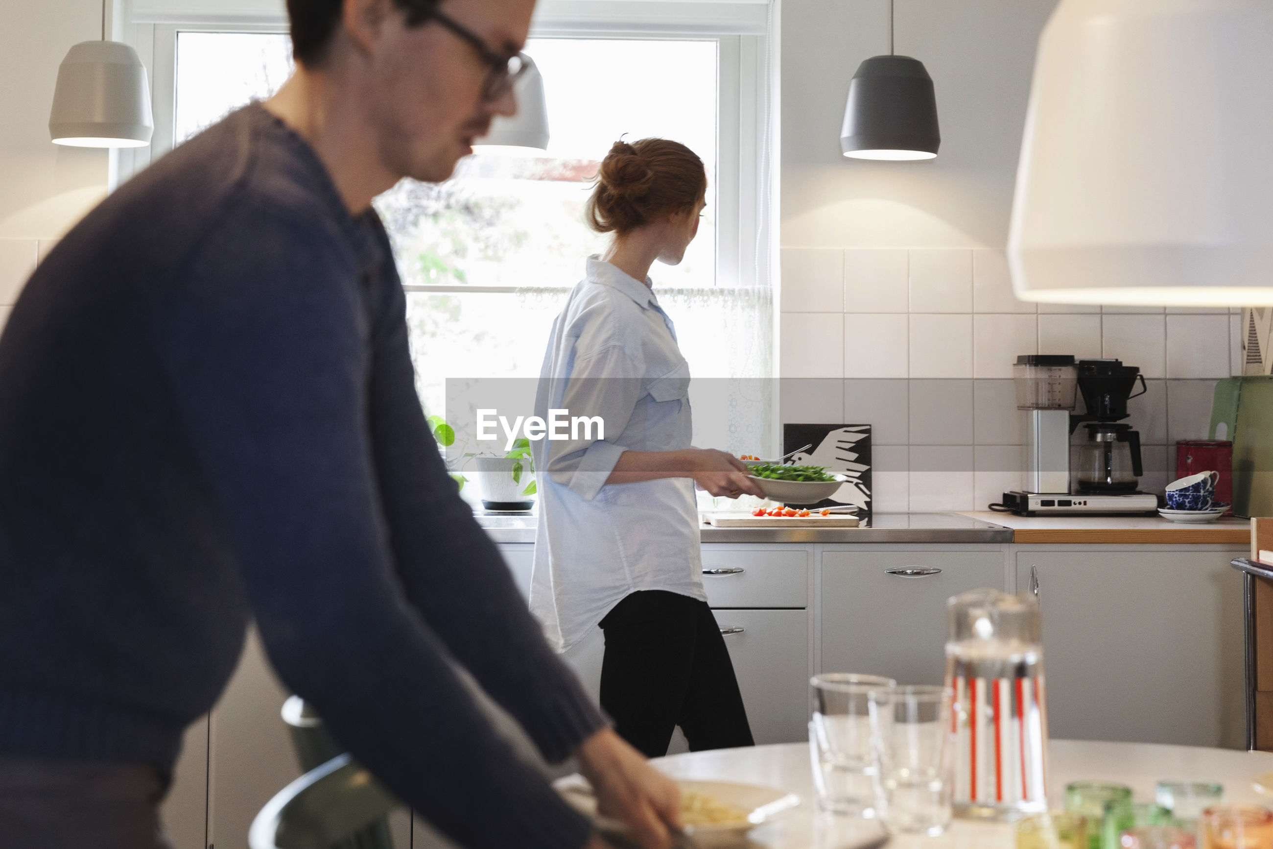 MAN AND WOMAN STANDING IN FRONT OF KITCHEN
