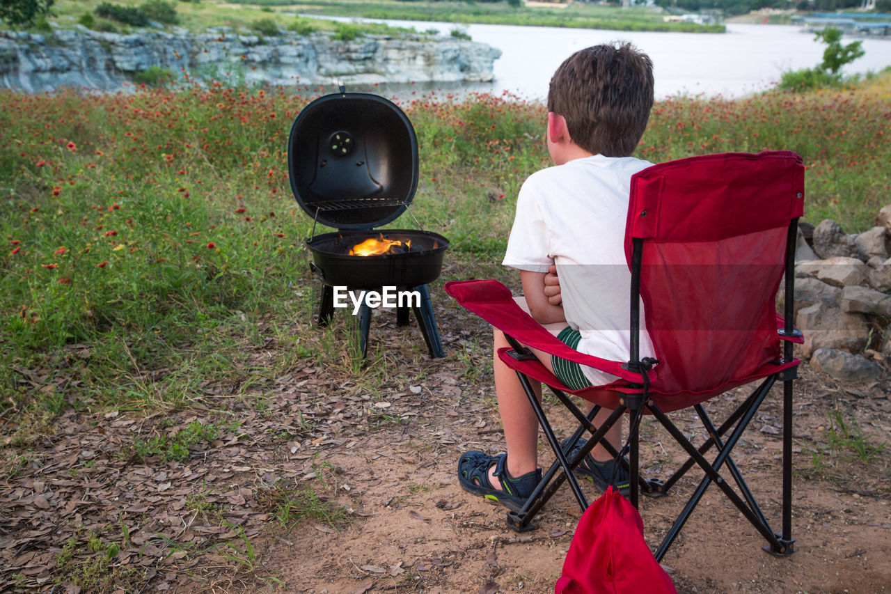 Rear View Of Boy Sitting On Chair With Burning Camping Stove