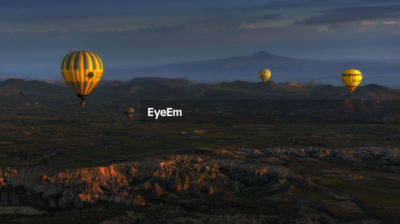 hot air balloon, mid-air, flying, ballooning festival, rock formation, adventure, rock - object, transportation, sky, mountain, rock hoodoo, scenics, landscape, nature, outdoors, air vehicle, tranquil scene, sunset, beauty in nature, no people, parachute, day