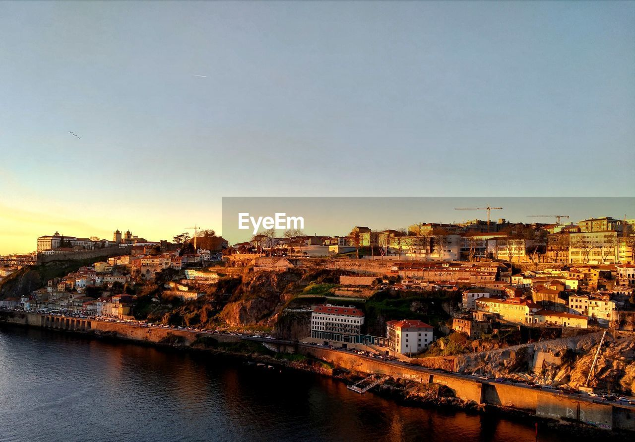 architecture, building exterior, built structure, sky, city, water, building, residential district, clear sky, nature, river, no people, cityscape, copy space, waterfront, outdoors, transportation, high angle view, sunset, townscape
