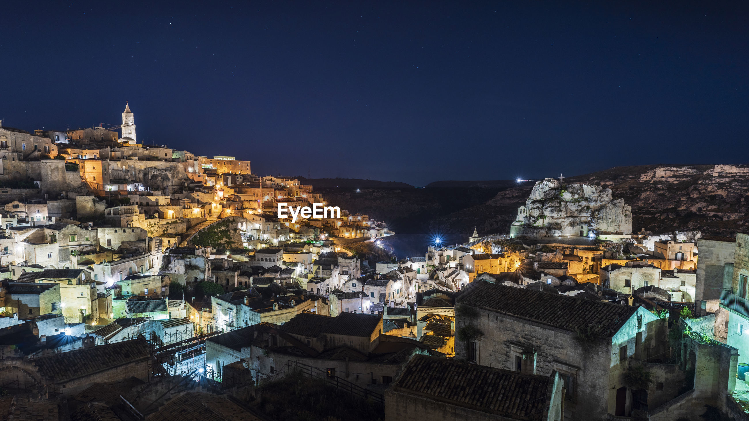 HIGH ANGLE SHOT OF ILLUMINATED TOWNSCAPE AGAINST SKY AT NIGHT