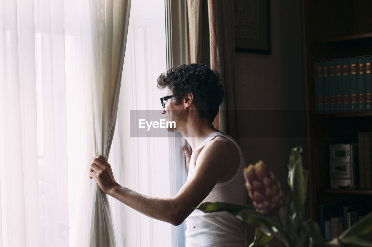 Young Man Standing By Window At Home