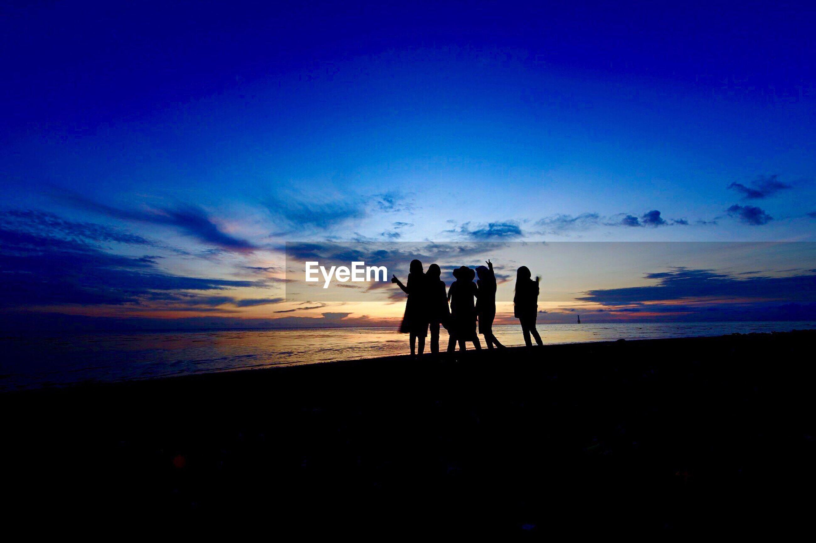 Silhouette of friends enjoying on beach