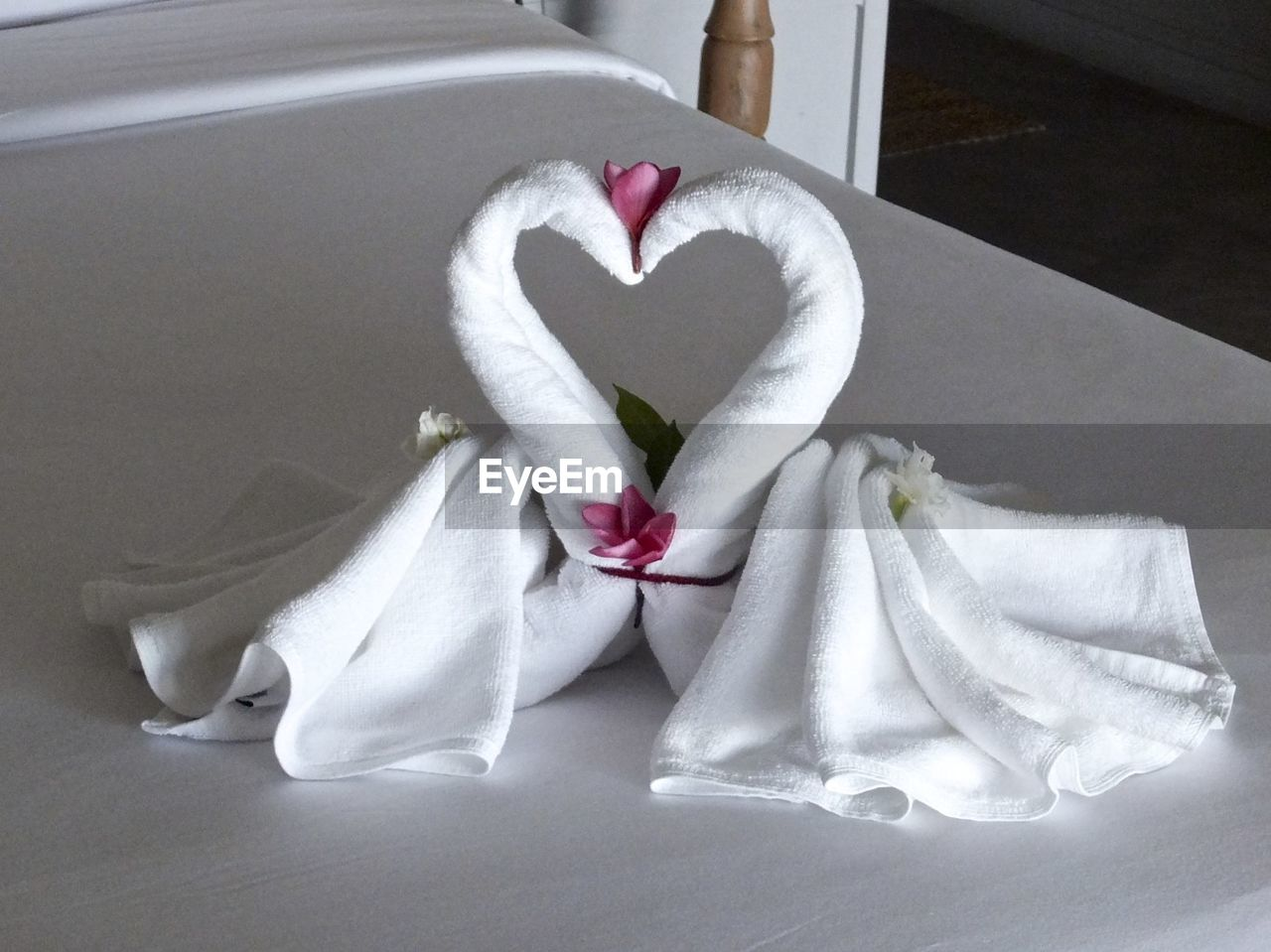 Swan made of white fabric in heart shape on bed