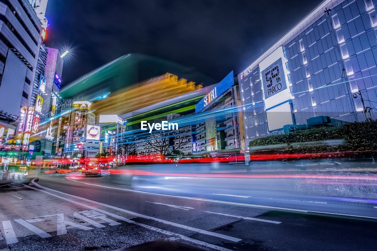 motion, long exposure, illuminated, built structure, building exterior, architecture, blurred motion, city, speed, night, transportation, light trail, road, street, building, sky, office building exterior, mode of transportation, no people, city life, cityscape, skyscraper