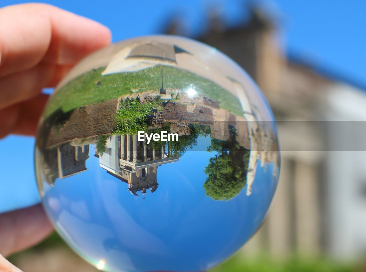 human hand, hand, holding, human body part, sphere, close-up, focus on foreground, one person, real people, day, blue, nature, finger, unrecognizable person, human finger, outdoors, body part, architecture, lifestyles