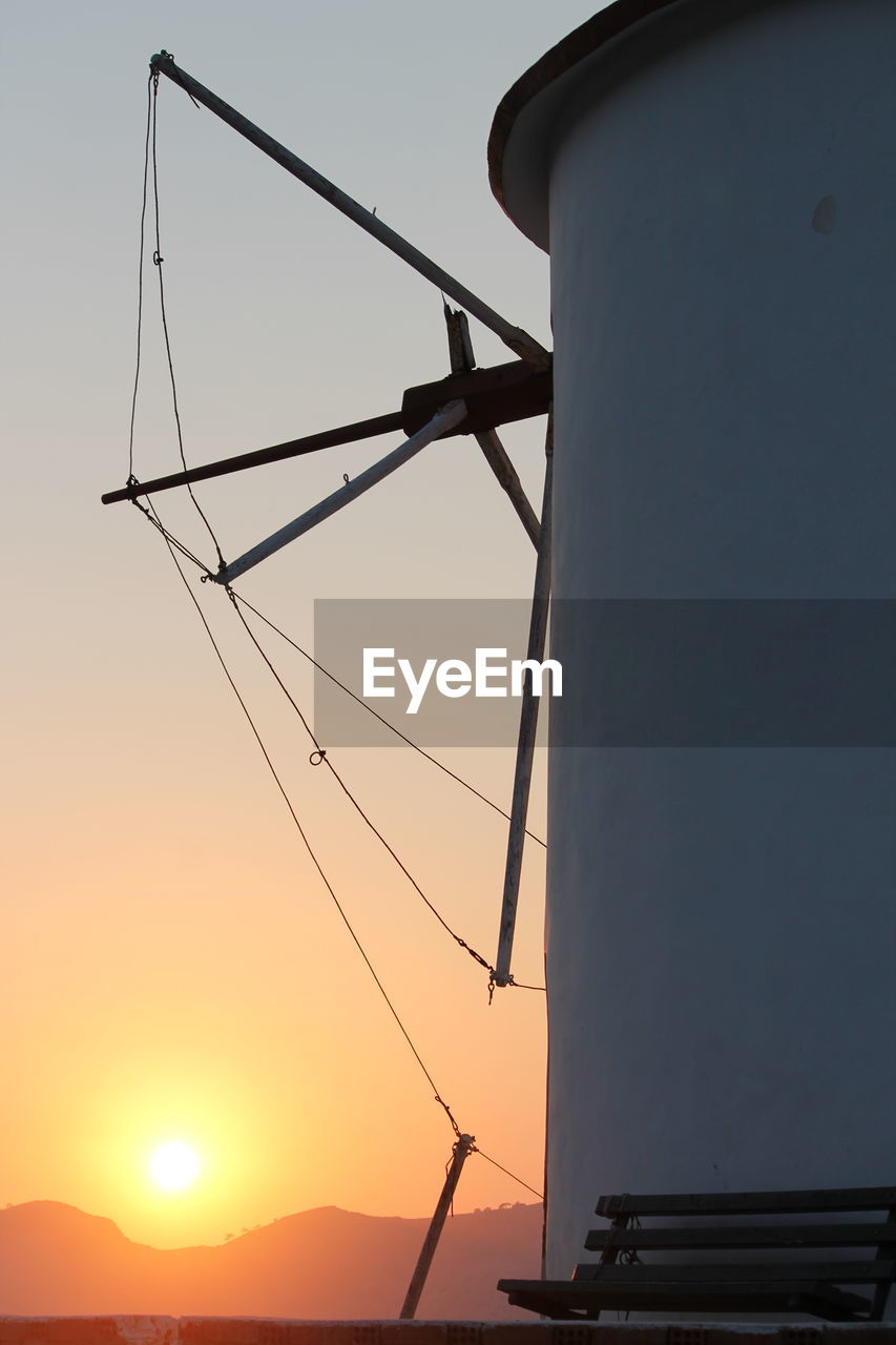 sunset, sky, fuel and power generation, wind turbine, technology, turbine, environmental conservation, alternative energy, renewable energy, environment, nature, traditional windmill, wind power, no people, low angle view, orange color, sun, outdoors, silhouette, built structure, electricity, power supply