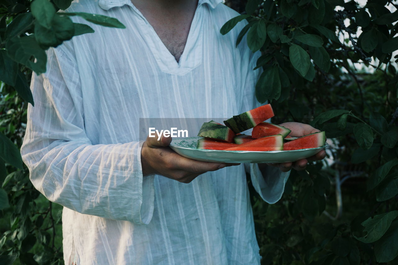 one person, food, vegetable, food and drink, real people, freshness, holding, midsection, healthy eating, fruit, tomato, day, standing, wellbeing, plant, lifestyles, nature, green color, leisure activity, hand