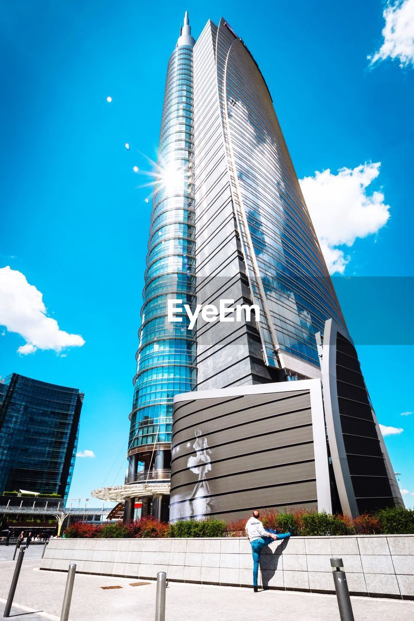 architecture, building exterior, built structure, real people, sky, day, one person, outdoors, low angle view, skyscraper, casual clothing, sunlight, cloud - sky, city, men, full length, modern, blue, standing, lifestyles, young adult, people