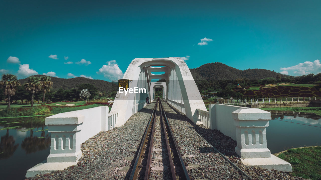 sky, nature, transportation, rail transportation, day, mountain, railroad track, track, no people, architecture, built structure, the way forward, blue, direction, water, mode of transportation, connection, cloud - sky, bridge, diminishing perspective, outdoors