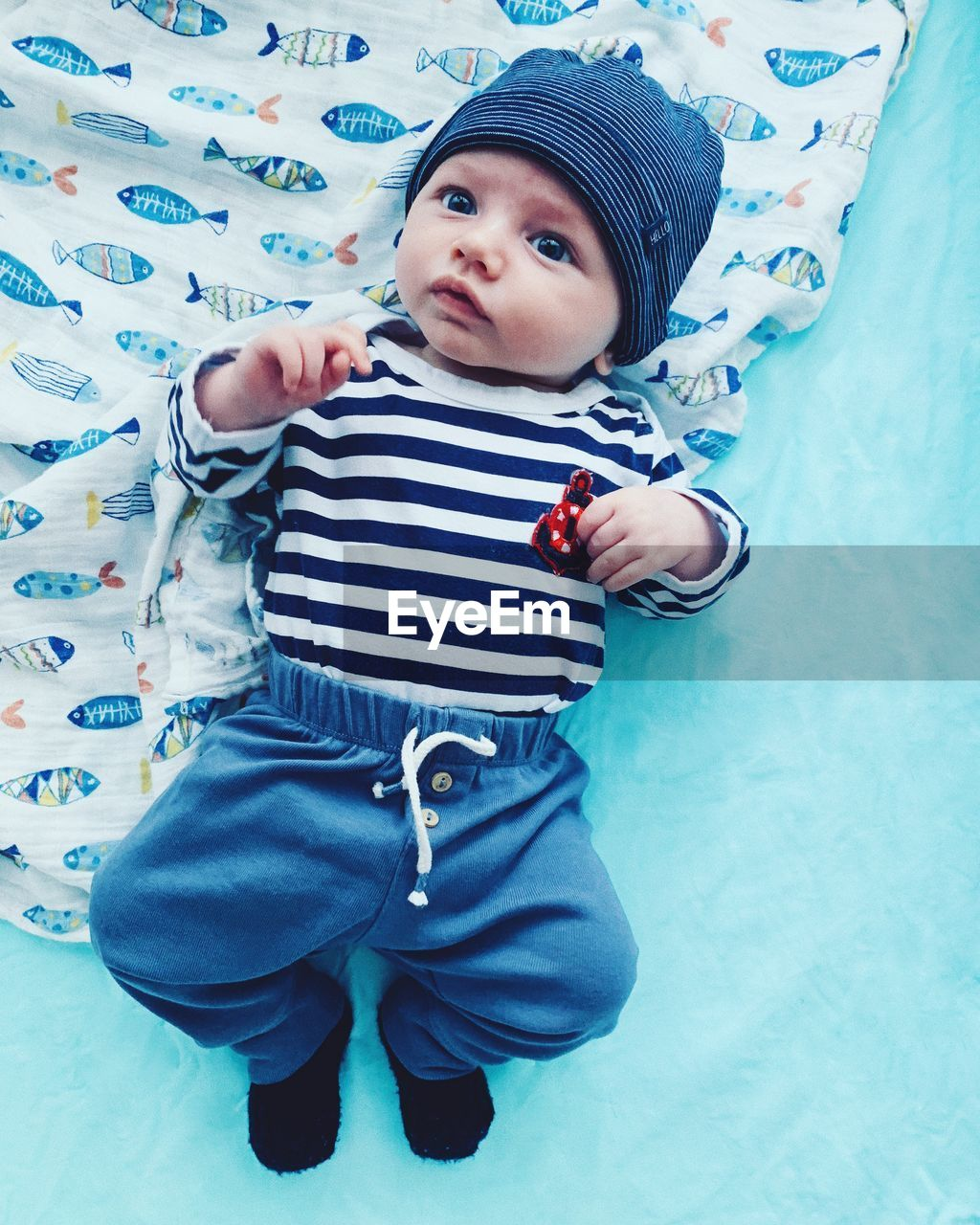 HIGH ANGLE VIEW OF BABY BOY STANDING ON BED