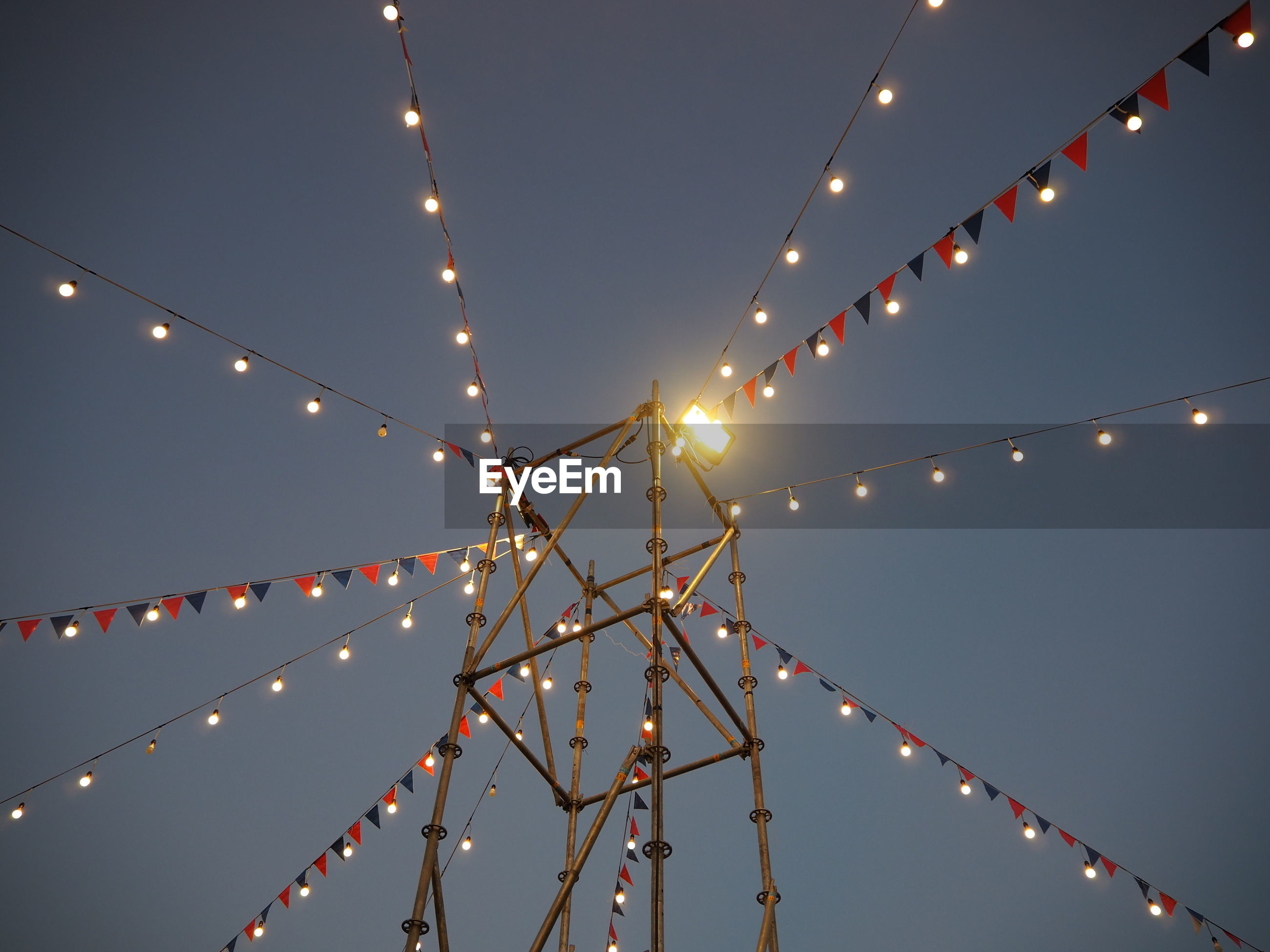 Low angle view of illuminated lighting equipment and buntings hanging against sky at dusk