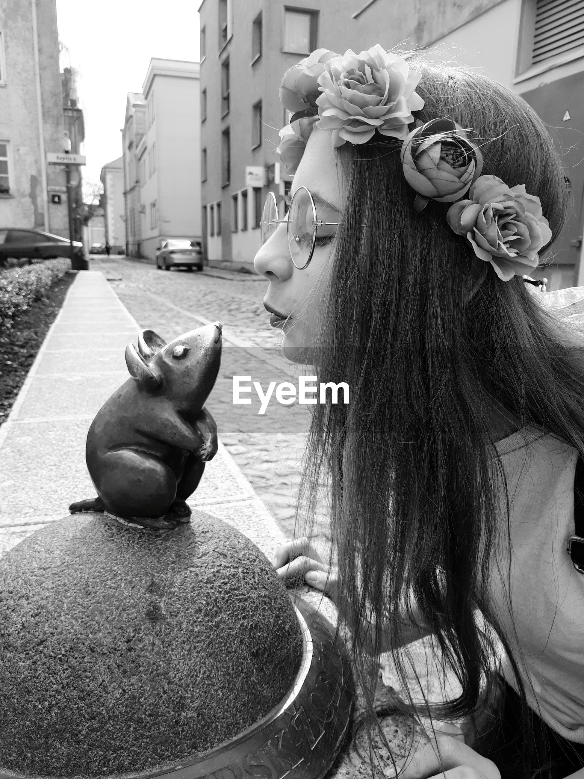 Side view of girl kissing rat statue outdoors